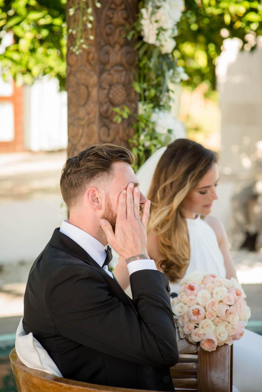 poolside wedding ceremony palm trees groom crying