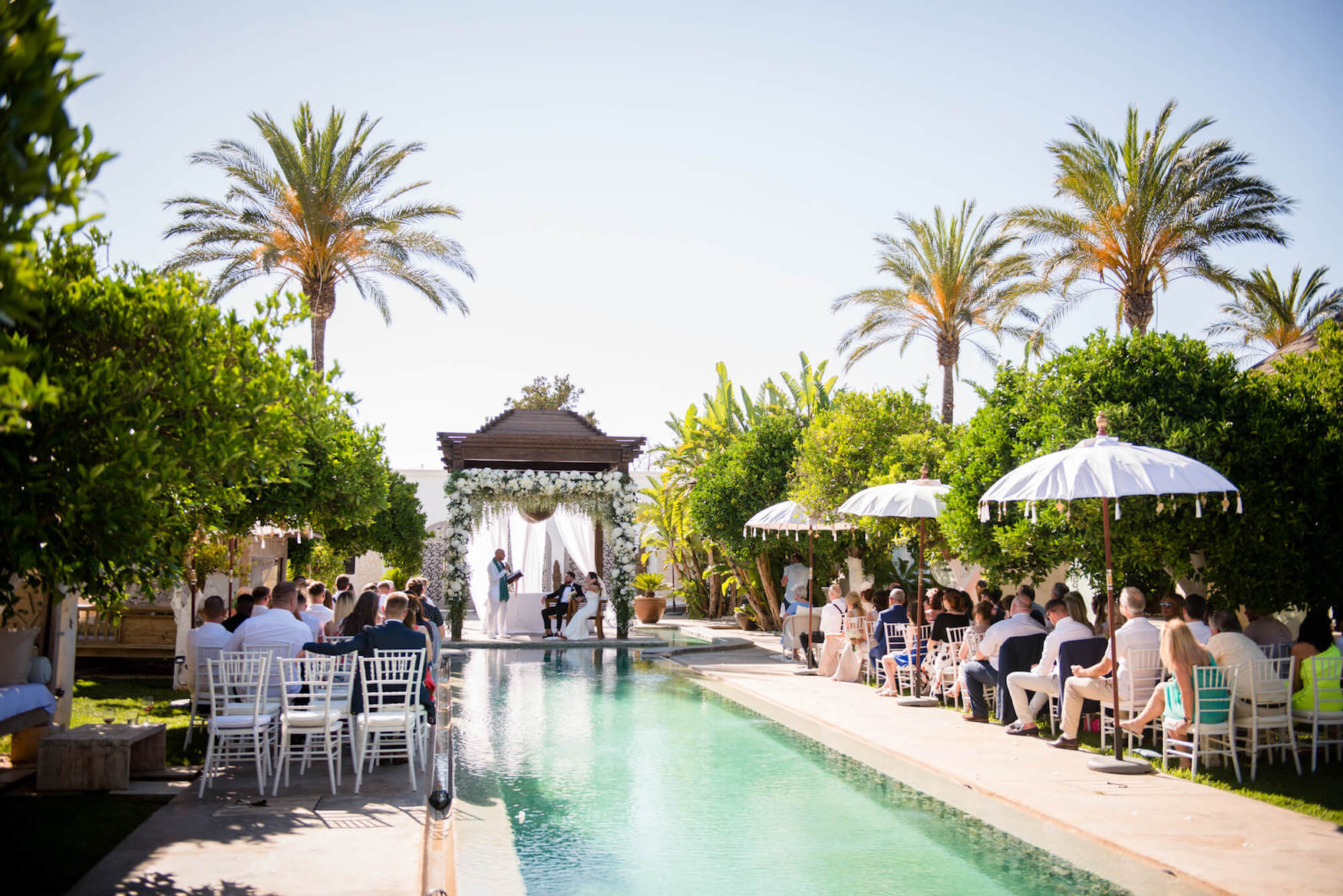 poolside wedding ceremony palm trees sunny skies