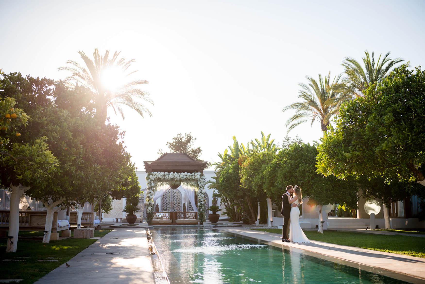 poolside kiss bride groom weding flower arch