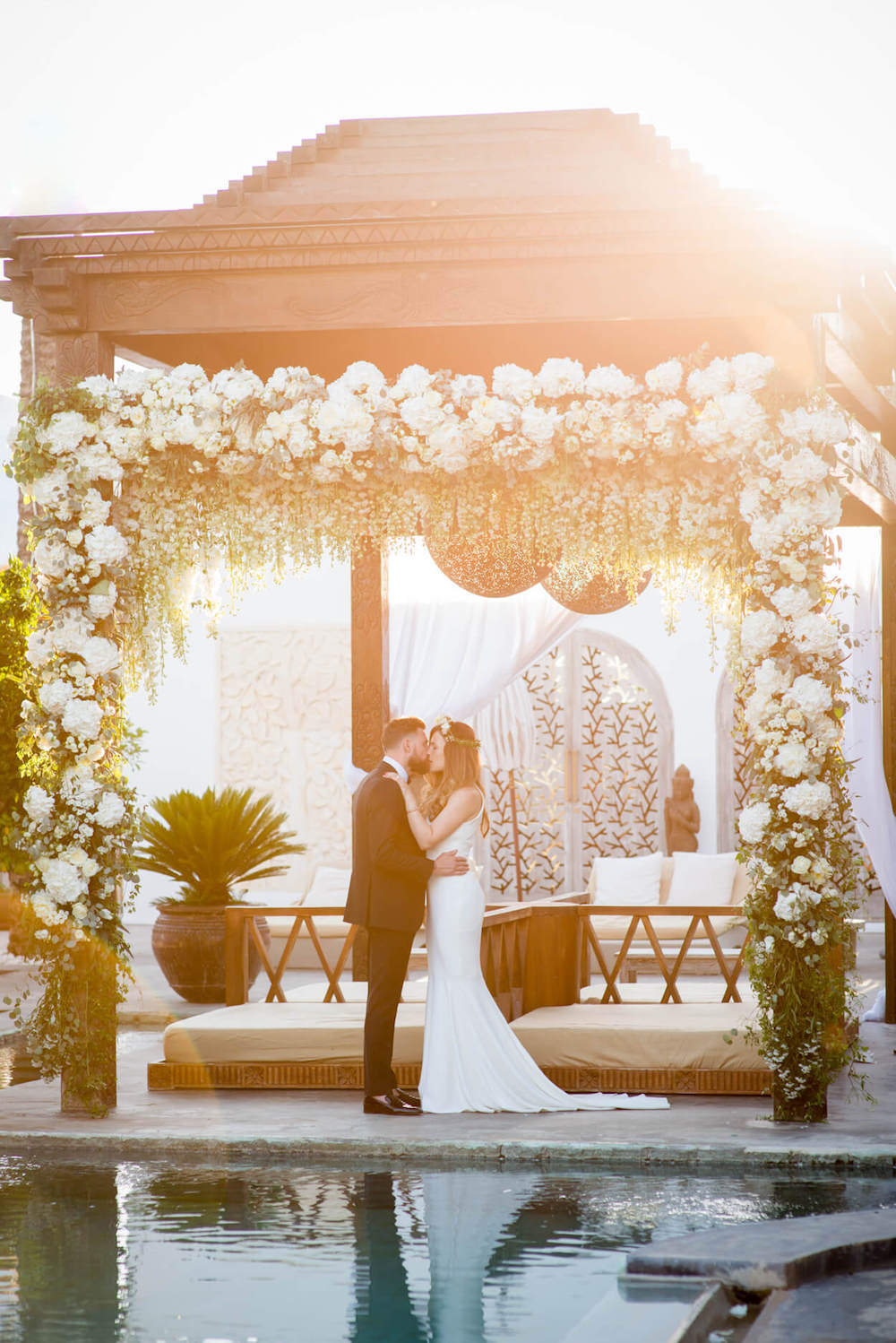 flower arch bride groom kiss sunset