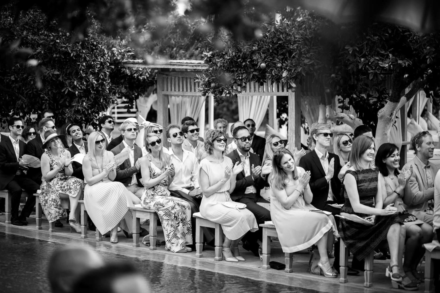 wedding guest clapping poolside ceremony