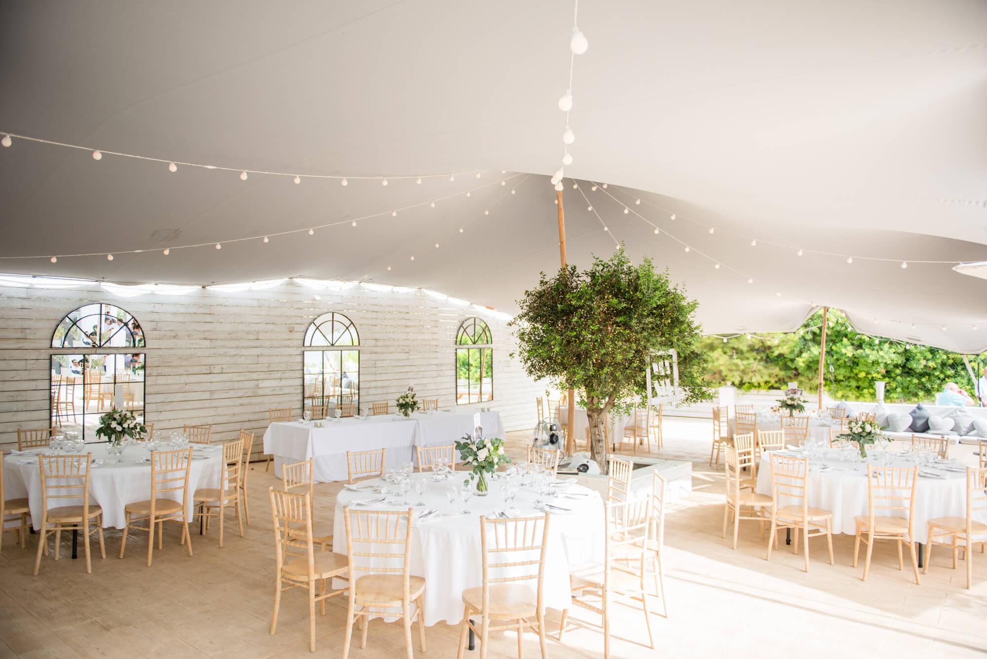 dinner tent wedding tables white rose table centers festoon lights seaside venue