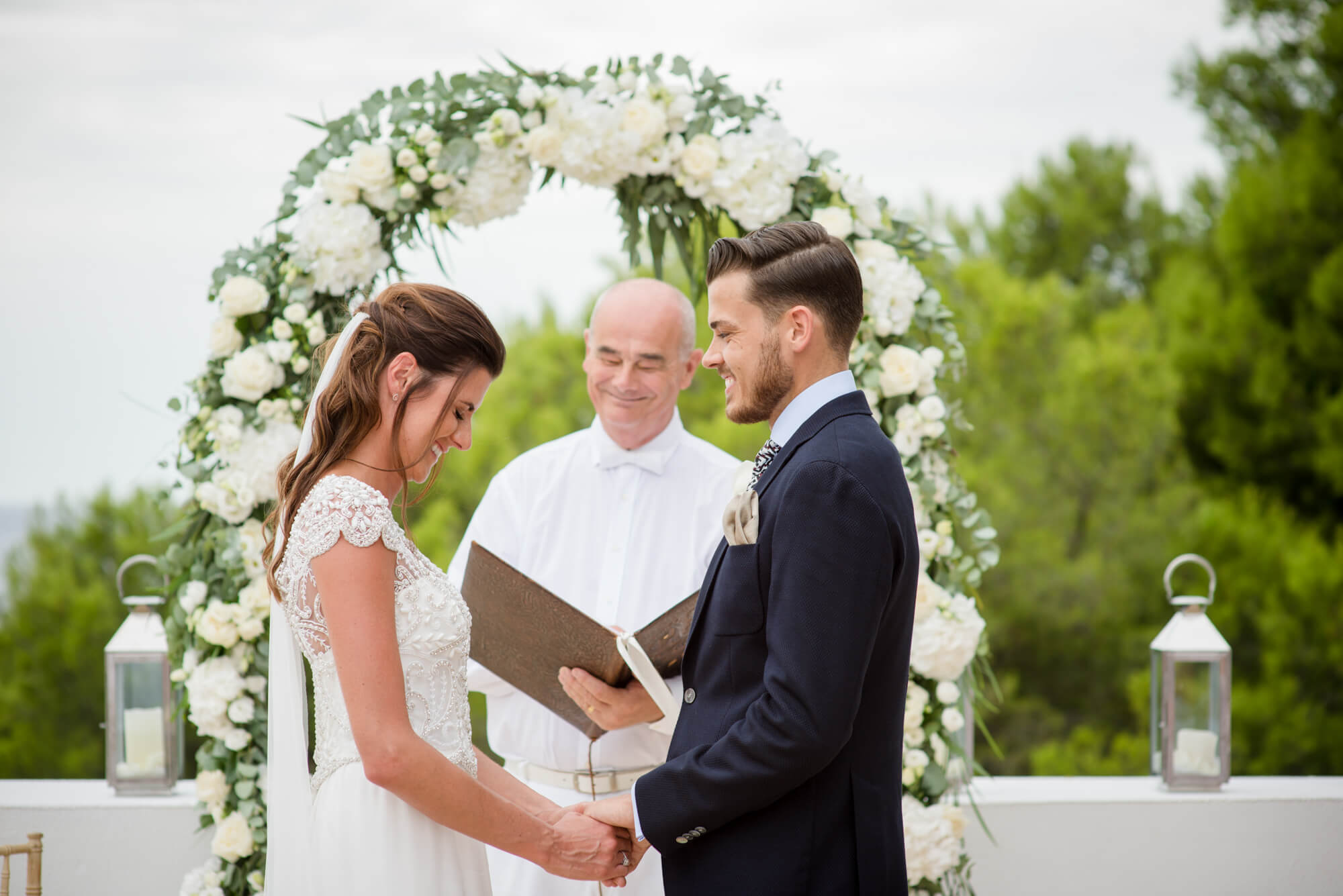 bride groom ceremony vows white flower arch wedding flowers