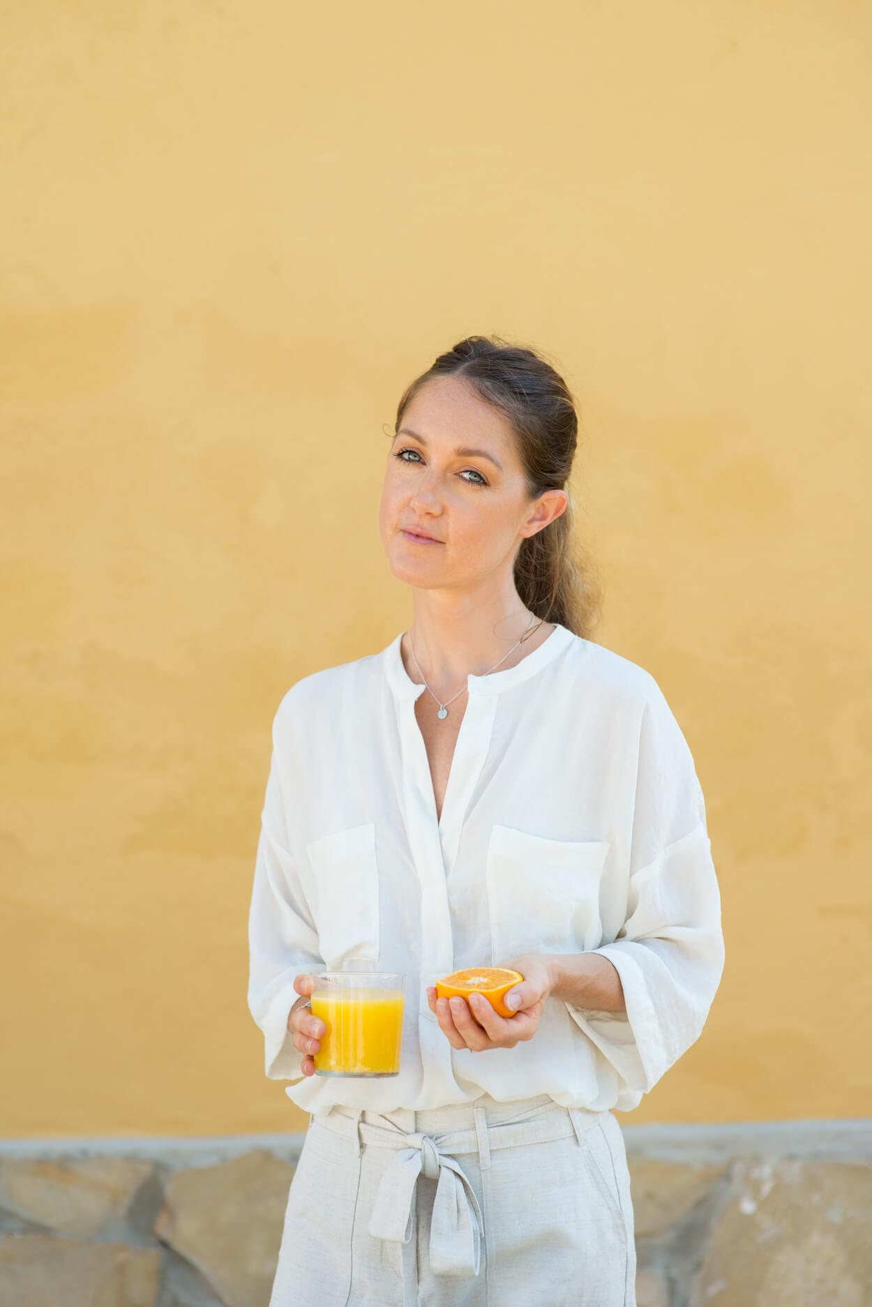 leanne portrait naturopath health coach with orange juice
