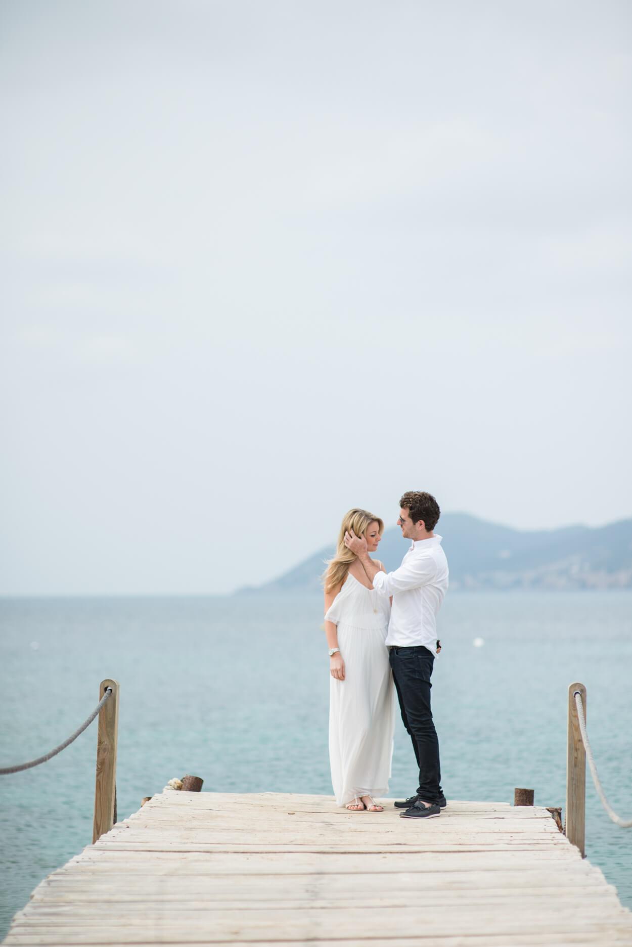 couple portrait boat pier engagement shoot blue sea background