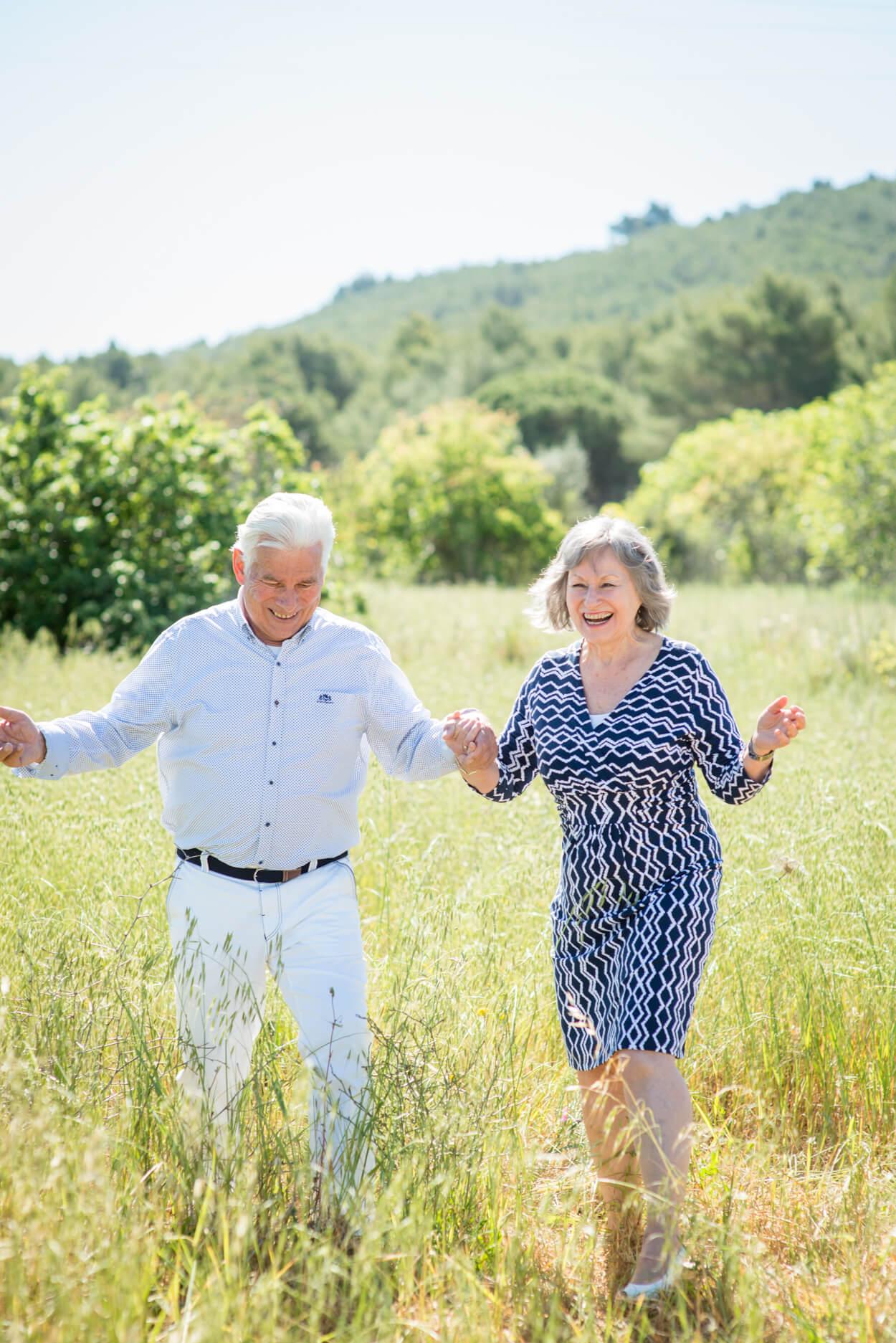 50th wedding anniversary couple portrait happy dancing in field