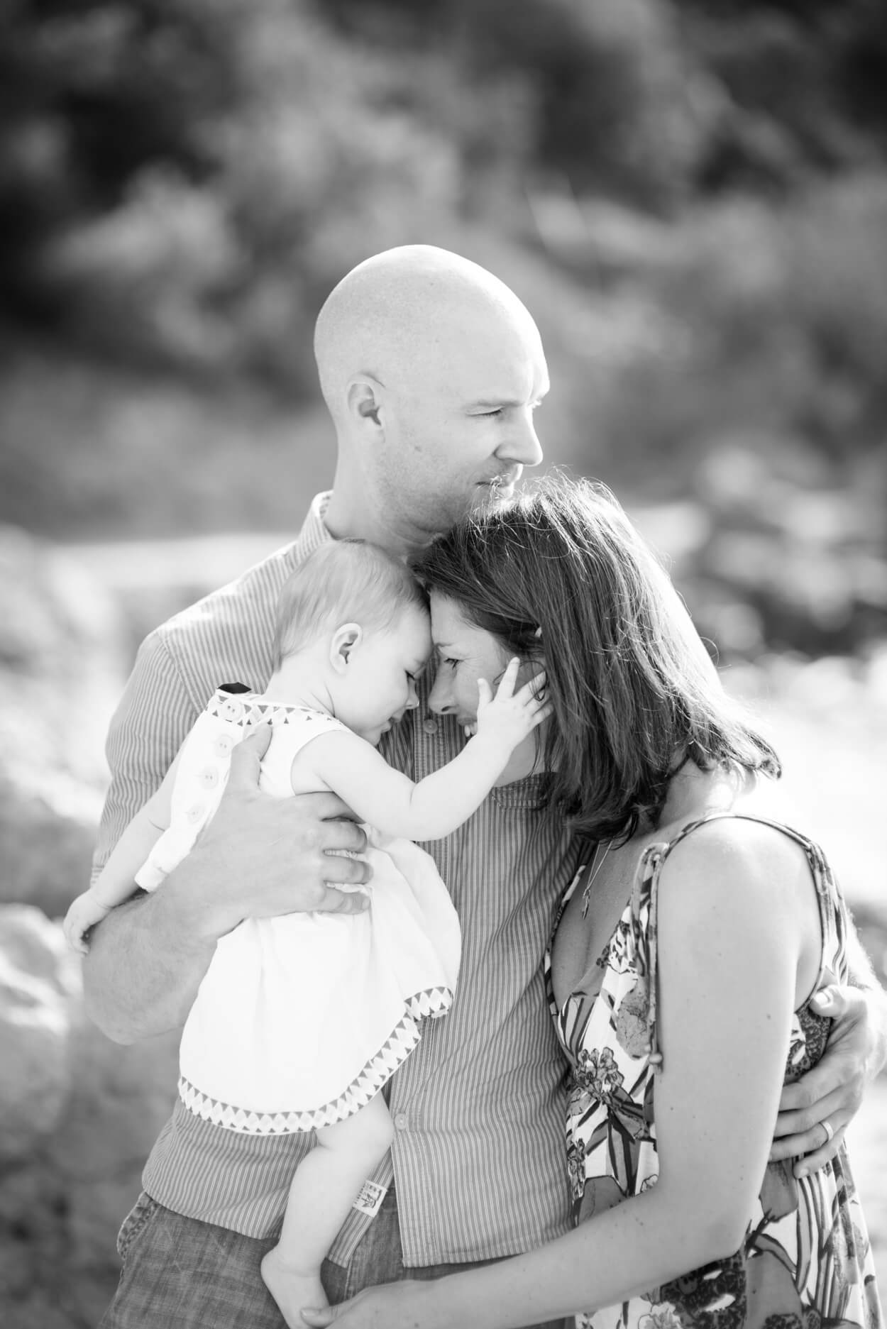 mother daughter father family cuddle portrait beach natural morning light