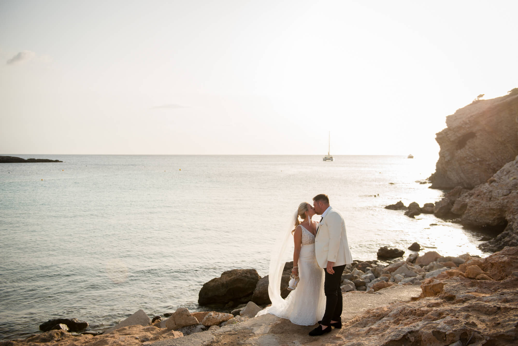 sunset bride groom portrait kiss beach side horizon veil blowing wind