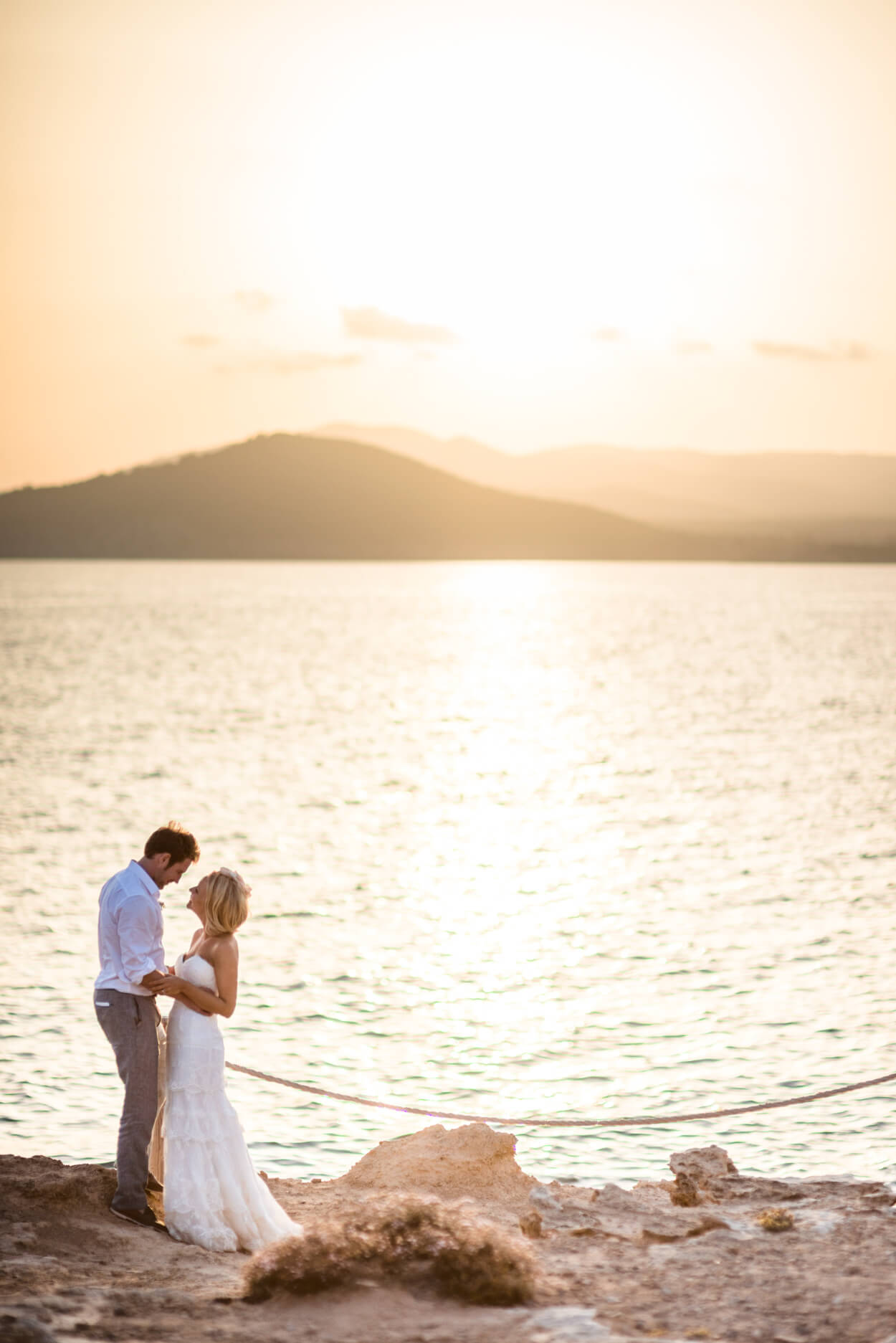 sunset wedding couple portrait beach side wedding venue hill