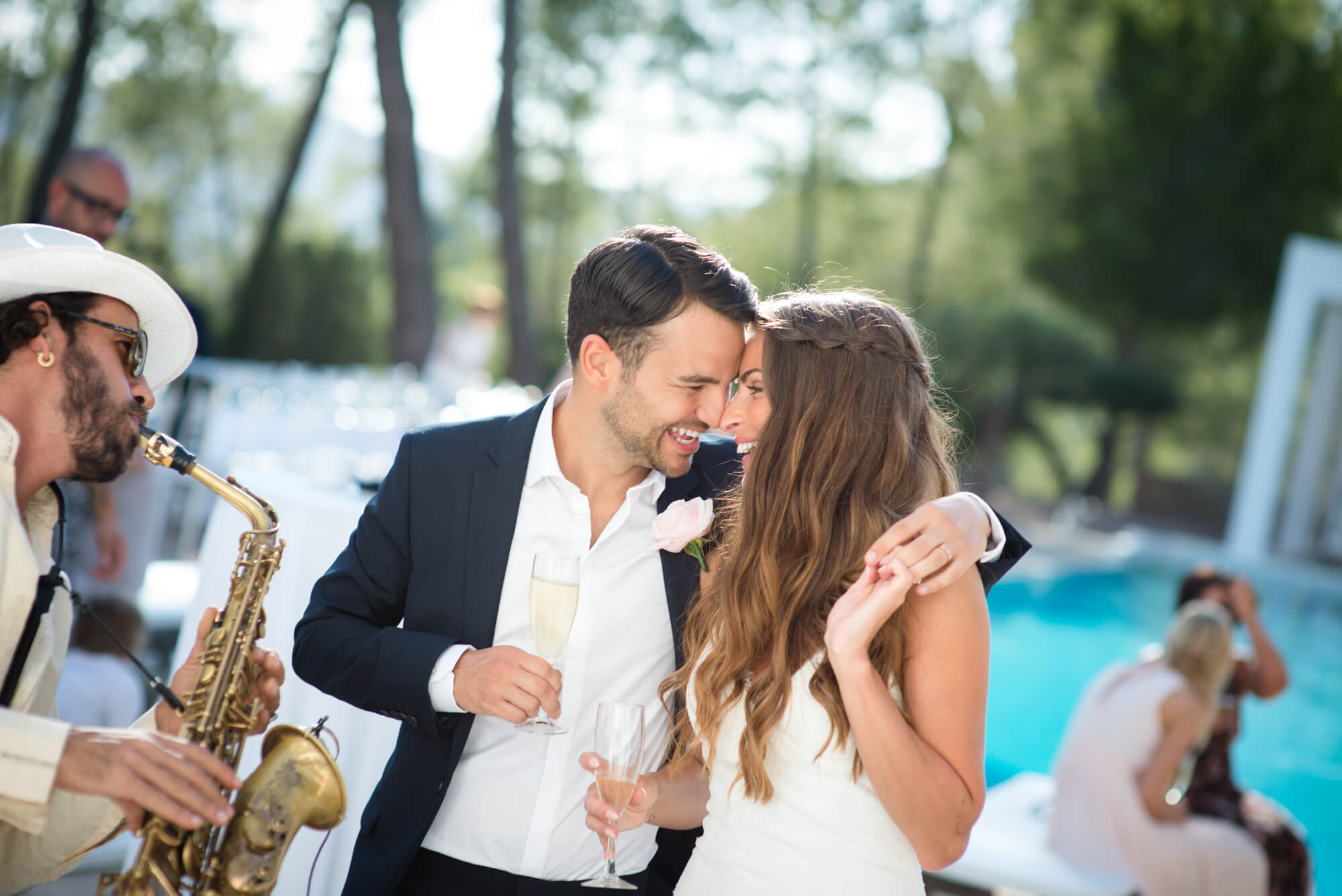 happy couple champagne cocktail hour poolside reception saxophonist