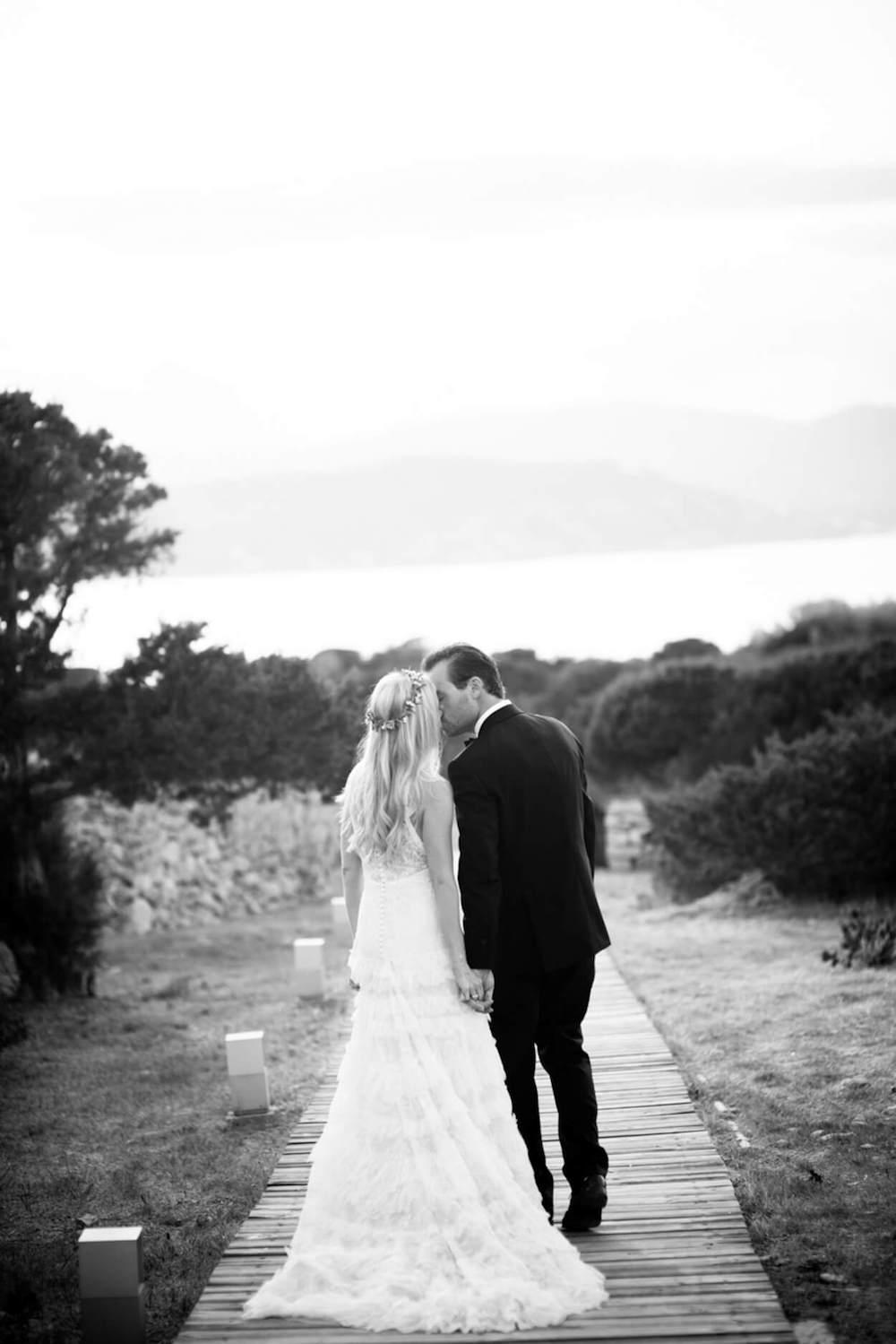 bride groom walk holding hands seaside kiss flower garland